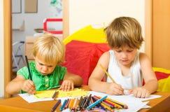 Siblings die met potloden spelen Stock Afbeeldingen