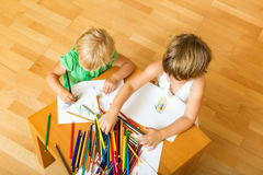 Siblings die met potloden spelen Stock Afbeelding