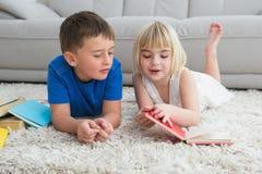 Siblings die op het verhalenboek van de vloerlezing leggen Royalty-vrije Stock Afbeelding