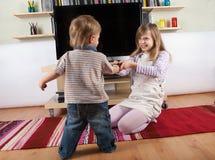 Siblings die over de afstandsbediening vechten Royalty-vrije Stock Foto