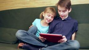 Siblings die panning van de tabletcomputer gebruiken stock video