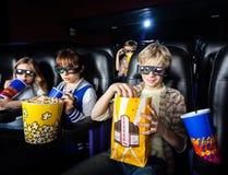 Siblings die Snacks in 3D Bioskooptheater hebben Stock Foto's