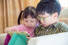 Siblings die spelen op tabletcomputer spelen stock foto