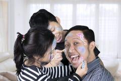 Siblings die tijd hebben die gezicht het schilderen doen aan hun vader Royalty-vrije Stock Afbeelding
