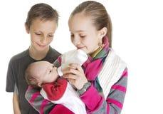Siblings die voor hun nieuwe Broer van de Baby geven Royalty-vrije Stock Foto's