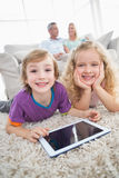 Siblings with digital tablet lying on rug Royalty Free Stock Photos