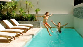 Siblings diving into the swimmingpool Stock Photography