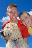 Siblings with dog. Brother and sister with their wheaten terrier dog Stock Image