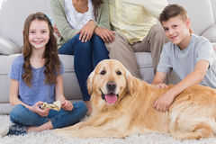 Siblings with dog and parents sitting behind Royalty Free Stock Photos