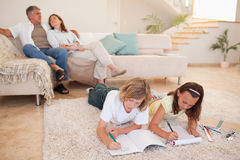 Siblings doing homework on the floor with parents behind them Royalty Free Stock Image