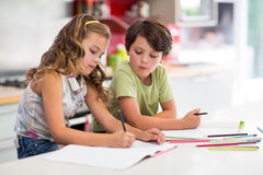 Siblings doing homework in kitchen. At home Royalty Free Stock Photography