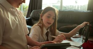 Siblings doing homework. Little girl and her brother are doing homework together using digital tablets stock footage