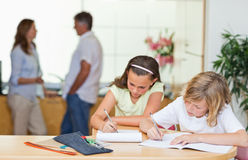 Siblings doing homework with parents behind them Stock Photos