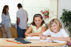 Siblings doing homework with their parents behind them Royalty Free Stock Image