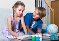 Siblings doing ordinary homework together Stock Photo