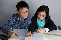 Siblings doing school homework Stock Images