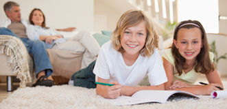 Siblings doing their homework on the floor with parents behind t Stock Photo