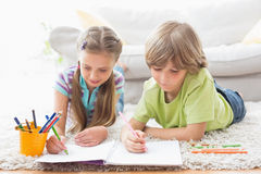 Siblings drawing with colored pencils while lying on rug Royalty Free Stock Images