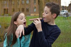 Siblings eating a bar of chocolate
