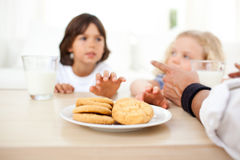 Siblings eating biscuits and drinking milk Royalty Free Stock Photography