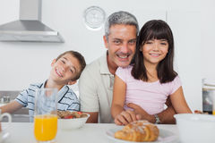 Siblings eating breakfast in kitchen together with dad Stock Image