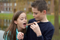 Siblings eating chocolate. Happy siblings , brother shares  a bar of  chocolate  with his sister Stock Images