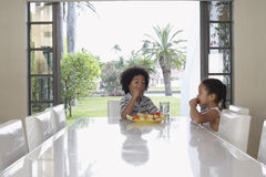Siblings Eating Fruit Salad At Dining Table Stock Images