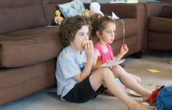 SIBLINGS EATING SANDWICH IN LOUNGE FLOOR Royalty Free Stock Images