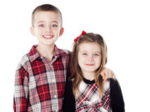 Siblings embracing in holiday clothes. In studio isolated on white Stock Image
