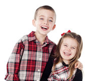Siblings embracing in holiday clothes. In studio isolated on white Stock Photos