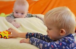 Siblings enjoy of toys. Baby is watching older brother. Stock Photos