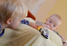 Siblings enjoy of toys. Baby is watching the older brother. Royalty Free Stock Images