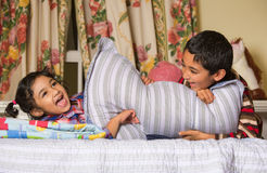 Siblings Enjoying a Pillow Fight Stock Photos