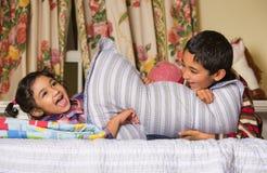 Siblings Enjoying a Pillow Fight. At Home Stock Photos