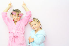 Siblings face  girl. Two little sisters are on the background of a pink wall in bath robes and home with curlers hairdo on the head Stock Photography