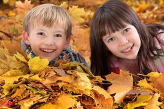 Siblings in fallen leaves. Smiling brother and sister looking out from piles of fallen leaves surrounding them Stock Photos