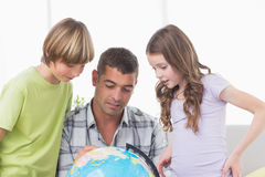 Siblings with father exploring map on globe Stock Photography