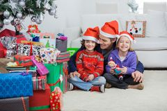 Siblings With Father At Home During Christmas Stock Photos