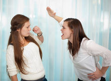 Siblings fighting. Sisters having an argument and getting physical with a fight Royalty Free Stock Photos