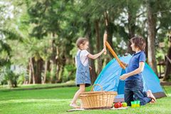 Siblings Fighting With Bread Loafs In Park. Happy siblings fighting with bread loafs by tent in park Royalty Free Stock Image