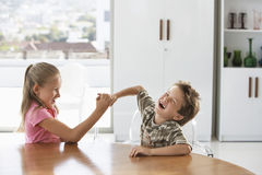 Siblings Fighting At Dining Table Royalty Free Stock Image