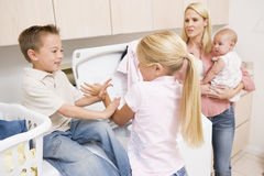 Siblings Fighting While Doing Laundry Royalty Free Stock Photo