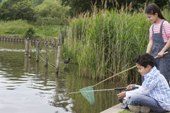 Siblings Fishing In Lake Stock Images
