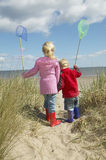Siblings With Fishing Nets Walking On Beach Royalty Free Stock Image