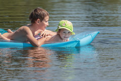 Siblings floating on inflatable azure pool air mat in summer pond outdoor Royalty Free Stock Images