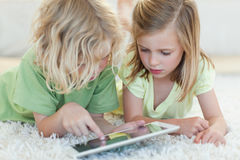 Siblings on the floor using tablet royalty free stock photos
