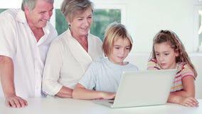 Siblings and grandparents using laptop Stock Photos