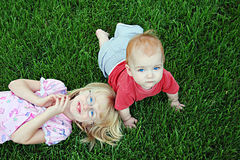 Siblings on grass. A little girl playing with her baby brother in the lawn Stock Photo