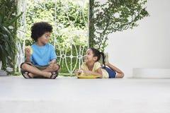 Siblings Having Breakfast On Porch Stock Photos