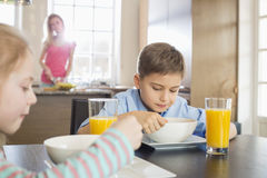 Siblings having breakfast at table with mother preparing food in background Royalty Free Stock Photo